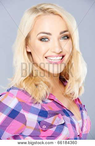 Happy sexy busty young blond woman with a beaming smile and laughing eyes looking at the camera  on grey