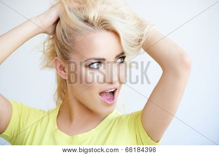 Frustrated blond woman mussing up her long hair in desperation as she calls out while looking to the right of the frame  head and shoulders on grey