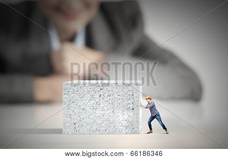 Businesswoman looking at man in hardhat pulling brick wall