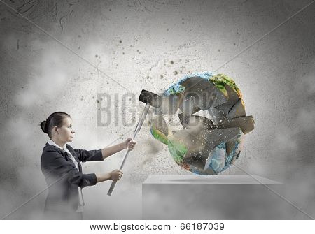 Businesswoman in anger crashing earth planet with hammer. Elements of this image are furnished by NASA