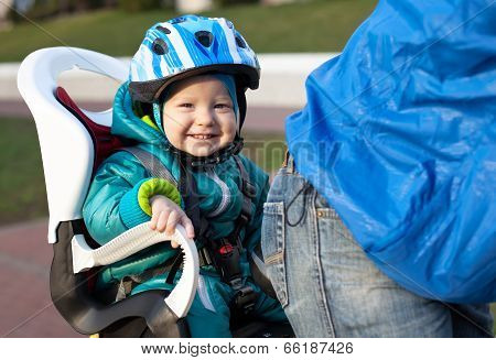 Little boy in the seat bicycle behind father