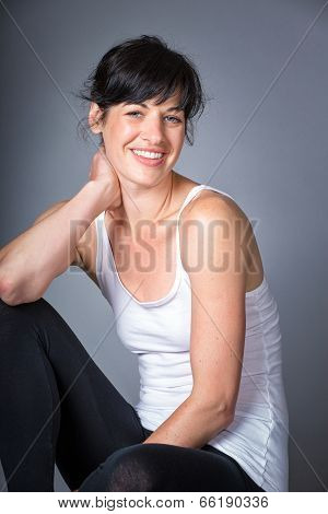 Athletic young woman relaxes, sitting