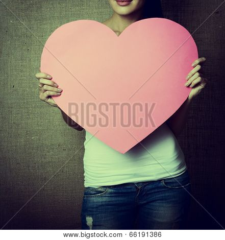 portrait of young woman holding pink heart incognito, love holiday valentine symbol over canvas background, toned