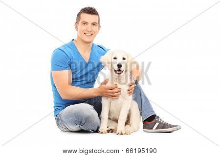 Young man sitting with his dog on the floor isolated on white background