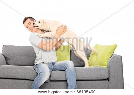 Man playing with a puppy seated on sofa isolated on white background