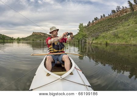 senior athletic paddler in a  decked expedition canoe photographing on a lake with green vegetation - Horsetooth Reservoir, Fort Collins, Colorado