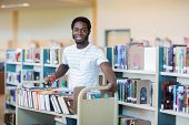 picture of librarian  - Portrait of young male librarian with trolley of books in library - JPG