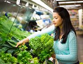 stock photo of local shop  - Closeup portrait beautiful pretty young woman in sweater picking up choosing green leafy vegetables in grocery store - JPG