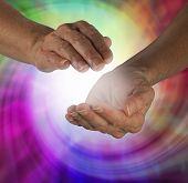 stock photo of kundalini  - Cupped healing hands with colorful spiral in background and ball of white energy between hands - JPG