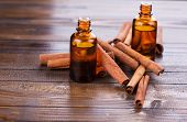 stock photo of cinnamon  - Essential aroma oil with cinnamon on wooden background - JPG