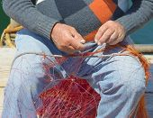 foto of fishnet  - Fisherman is repairing the fishnet. Close uo hands ** Note: Soft Focus at 100%, best at smaller sizes - JPG
