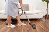 picture of maids  - Young Maid Cleaning Floor With Handheld Vacuum Cleaner - JPG