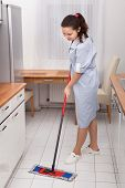 foto of maids  - Portrait Of Young Maid In Uniform Cleaning Kitchen Floor - JPG