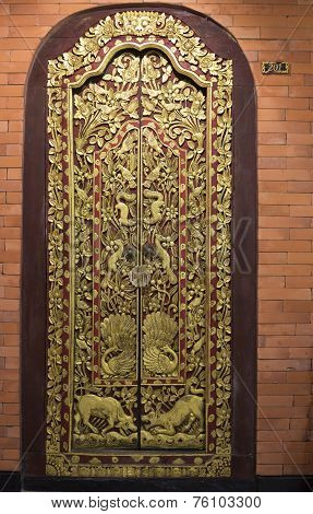 Richly ornamented, gilded wooden door in Indonesia