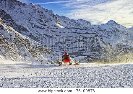 Red Helicopter Taking Off From Swiss Ski Resort Near Jungfrau Mountain