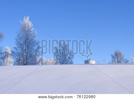 Snowy slope, blue sky, frost and a white tower.