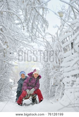 Boy And Girl At Sledging Through Snowy