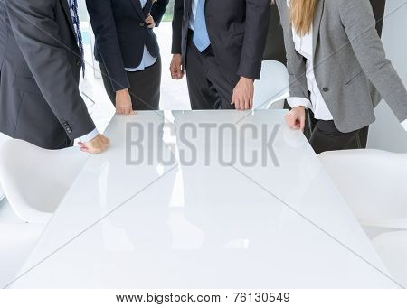 Unrecognizable business people standing around meeting table with lots of copy space
