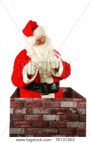 Santa Claus in a Chimney. Santa Claus smiles and points to you the viewer as he enters a chimney on Christmas eve. Santa Claus isolated on white with room for your text or graphics with clipping path