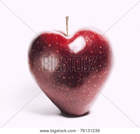 attractive teasing red apple in the shape of heart close up isolated