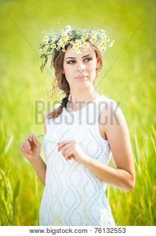 Young girl with wreath on golden wheat field.Portrait of beautiful blonde girl with wreath