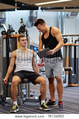 sport, fitness, equipment, technology and people concept - men with personal trainer and tablet pc computer exercising on gym machine