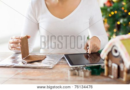 cooking, people, christmas and technology concept - close up of woman with tablet pc computer making gingerbread houses at home