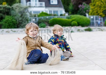 Two Little Children Sitting On Beach Of River Elbe And Playing Together With Sand