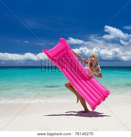 Woman standing with pink swimming mattress on tropical beach