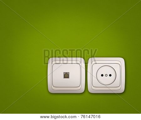 Computer And Electrical Outlets On Green Wall