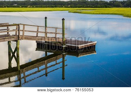 Boat Dock Reflecting In Inlet Marsh Water