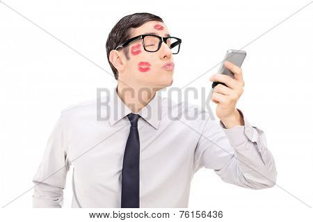 Man sending a kiss through a cell phone isolated on white background