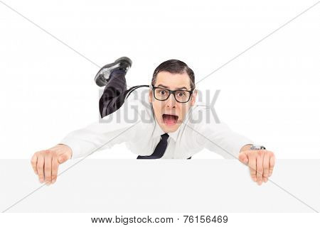 Scared man holding on to the edge of a panel isolated on white background