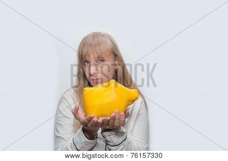 Blond Woman Shows Yellow Pig Monebox
