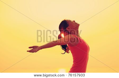 woman open arms under the sunrise at seaside