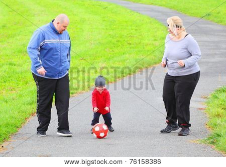 Overweight parents with her son playing soccer together.