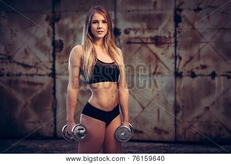 Attractive Young Woman Working Out With Dumbbells In An Abandoned Industrial Area- Bikini Fitness Gi