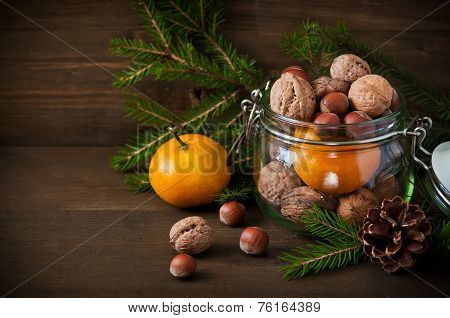 Christmas Concept (decoration). Jar  With Tangerine, Cone And Walnut  On Rustic Wooden Background