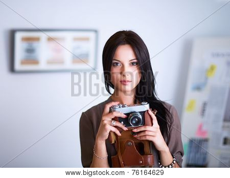 Young woman watching footage on film, standing near window