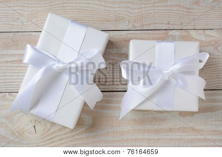 High angle image of two presents wrapped in white paper and ribbons. Horizontal format on a whitewashed rustic wood table.