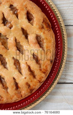 High angle closeup of an fresh baked lattice crust apple pie on holiday chargers. The dessert is on red and gold chargers on a white wood table. Vertical format.