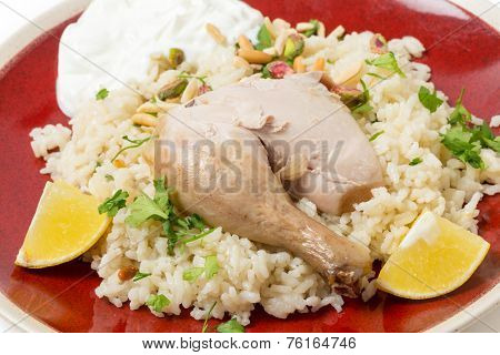 Chicken pilaf, or riz bi djaaj, traditional Arab and Mediterranean boiled chicken and rice dish, served with roasted nuts and lemon wedges.
