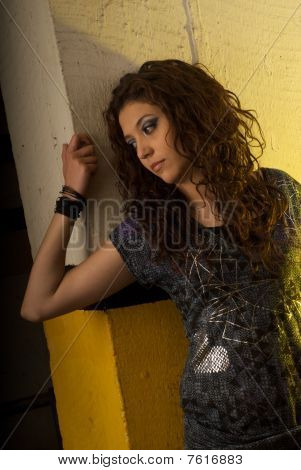 model pretty woman sitting against a wall gesturing