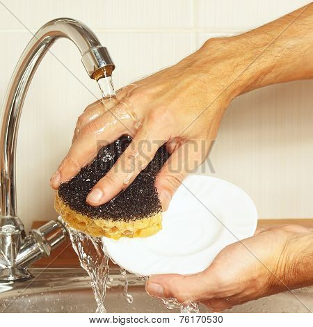 Hands with sponge wash the dishes under running water in kitchen