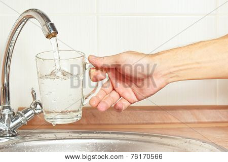 Hands pour water into the glass under the tap in kitchen