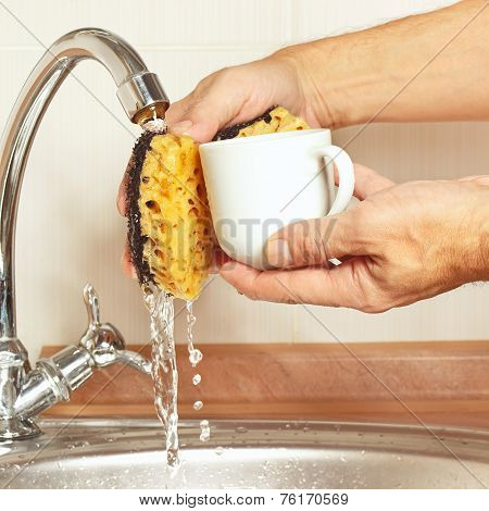 Hands wash the coffee cup under running water in kitchen
