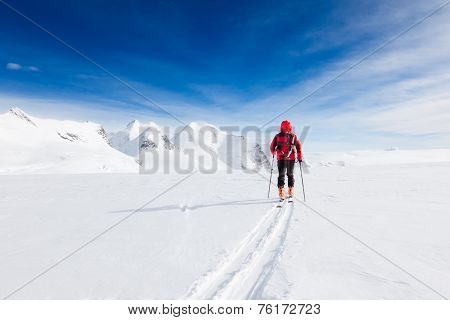 Mountaineer walking on a glacier during a high-altitude winter expedition in the european Alps. Breithorn, Monte Rosa massif, Valle d'Aosta, Italy, Europe.