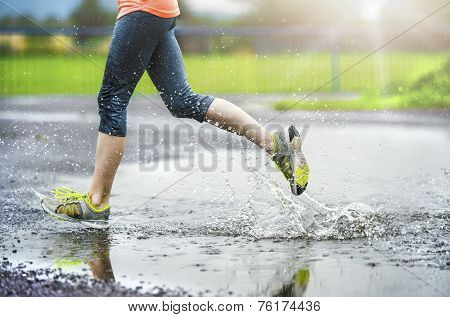 Girl of woman running in rainy weather - detail