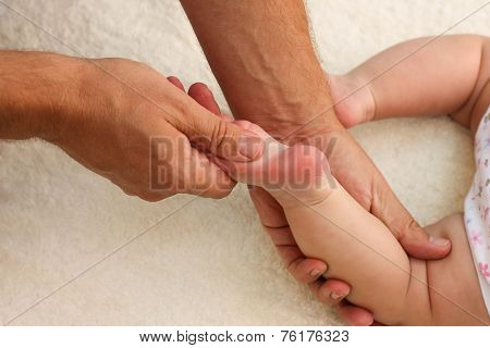 masseur doing massage for foot on little baby