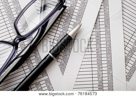 Eyeglasses And Pen On Top Of Business Reports